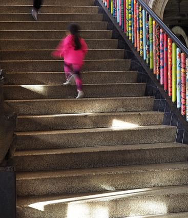 Girl running up main staircase